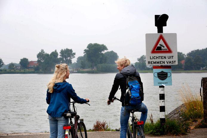 Fietsers Anniek en Tim op de veerstoep, tevergeefs, want de pont vaart niet.