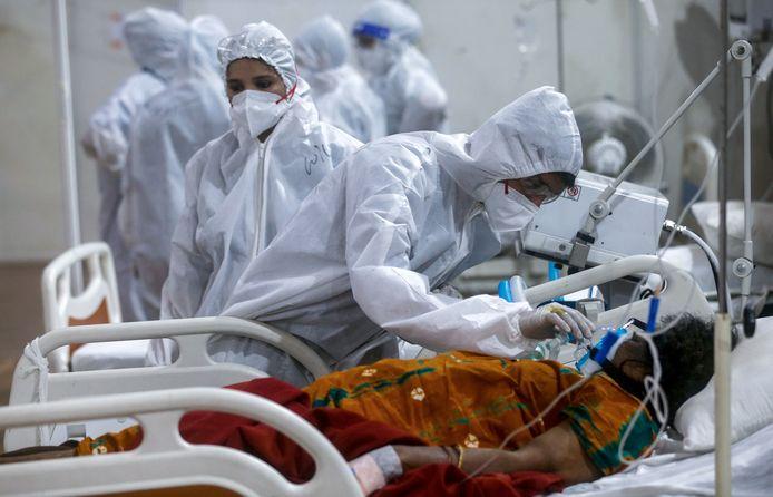 Gezondheidsmedewerkers bij een coronapatiënt in Mumbai.