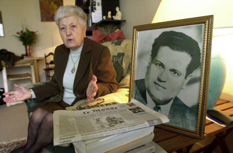 Malika Boumendjel, weduwe van Ali Boumendjel, tijdens een interview in 2001. Ze zit naast een ingelijste foto van haar man. Beeld AFP