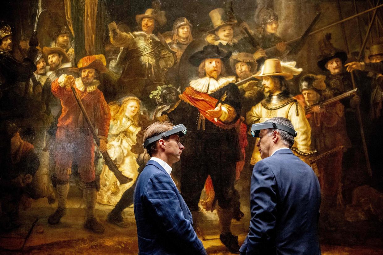 Twee museummedewerkers voor 'De Nachtwacht' bij de voorstelling van de restauratieplannen. Beeld AFP