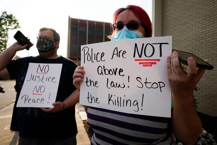 Burgers protesteren tegen de dodelijke schietpartijen door politieagenten: 'de politie staat niet boven de wet', staat er te lezen op het rechtse bordje. 'Stop het moorden!'