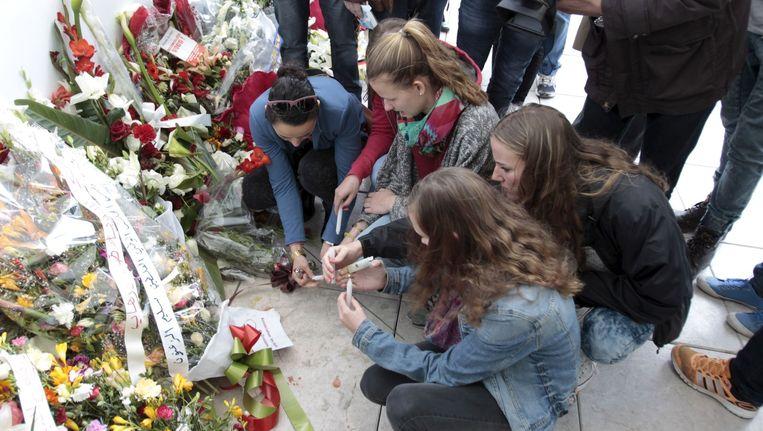 Toeristen branden kaarsen voor het Bardomuseum in Tunis, waar bij een aanslag twintig toeristen om het leven kwamen. Beeld reuters