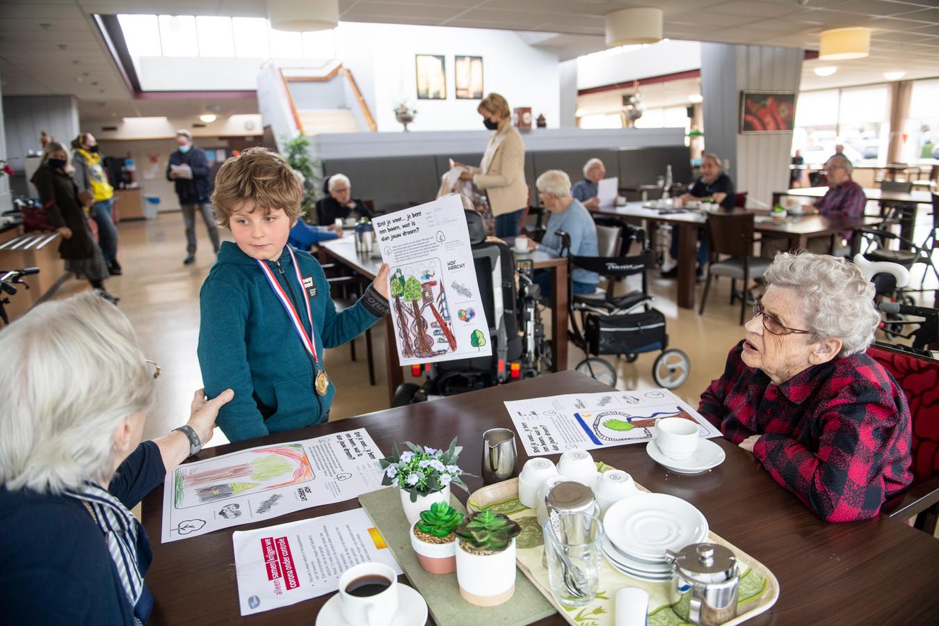 De 8-jarige Sander Hulsing reikt tijdens de koffie in zorgcentrum De Stoevelaar in Goor droomboomtekeningen van basisschoolleerlingen uit aan ouderen. Zijn winnende tekening houdt hij in zijn hand en geeft de jongen niet weg.