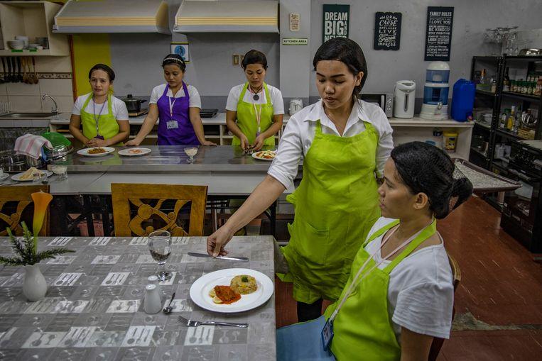 Op een school in de Filipijnse hoofdstad Manilla trainen vrouwen voor het certificaat huishoudelijk werk. Zonder dat diploma krijg je geen werkvisum. Beeld Ezra Acayan