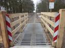 Een nieuw hek met veerooster bij het begrazingsgebied midden op de Maashorst.