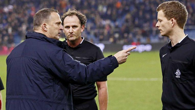 Van den Brom gaat verhaal halen bij de spelleiders na de match. Beeld ANP