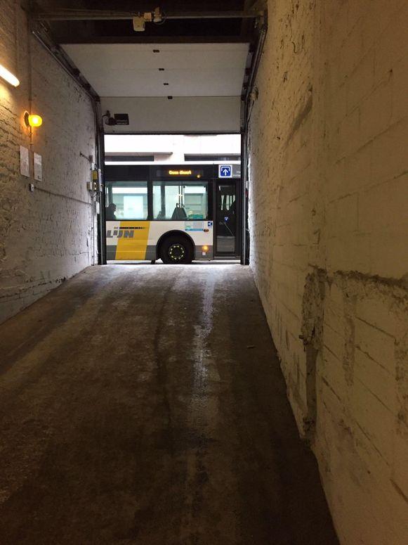 Een bus van De Lijn blokkeert de uitrit van een parkeergarage.