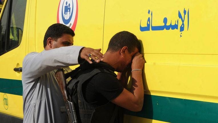 Een lid van de veiligheidsdienst reageert op de dood van zijn collega's. Beeld AP