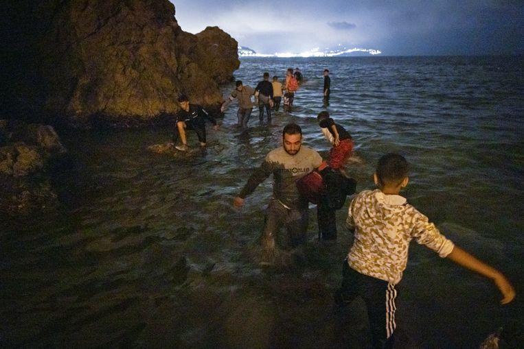 Voor het merendeel Marokkaanse migranten zwemmen en lopen vanuit Marokko door het ondiepe water om het Spaanse stadje Ceuta te bereiken.  Beeld AFP