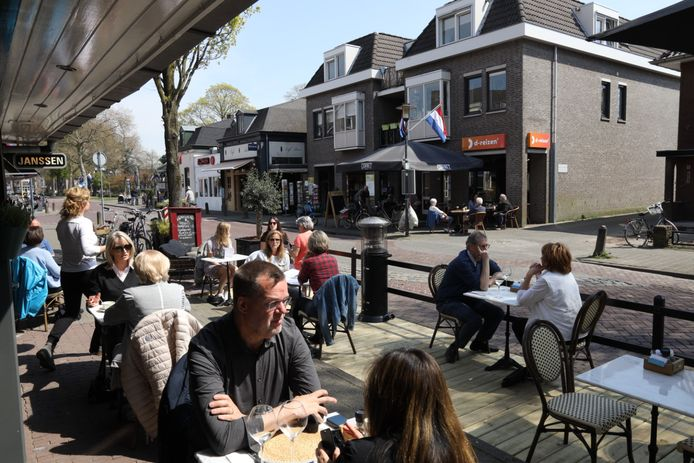 Volle terrassen in de Parkstraat in Nuenen. Aan de overzijde van de straat café René met het terras voor de gesloten winkel van D-reizen.