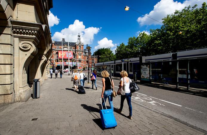 Toeristen met rolkoffers op het Leidseplein in Amsterdam. Het vervelende geluid van rolkoffers is een van de problemen van de toenemende populariteit van Airbnb.
