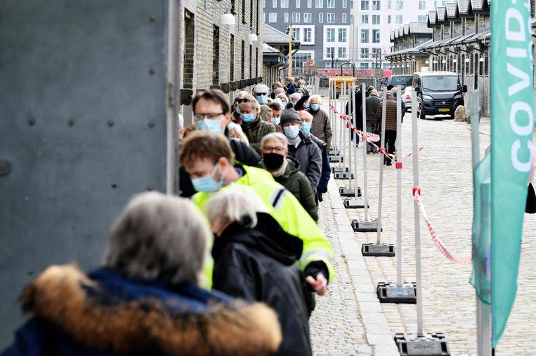 In Kopenhagen sluiten mensen aan in de rij voor hun vaccin. Ook voor tests wordt er volop aangeschoven in de Deense hoofdstad, zeker wanneer het weekend nadert.  Beeld AFP