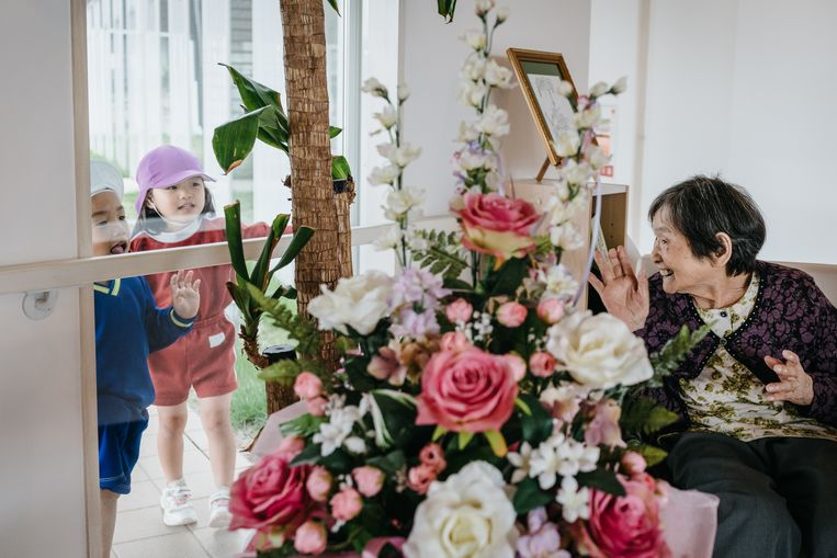 Miruka Umino (91) groet enkele kleuters. Beeld Jun Michael Park/laif