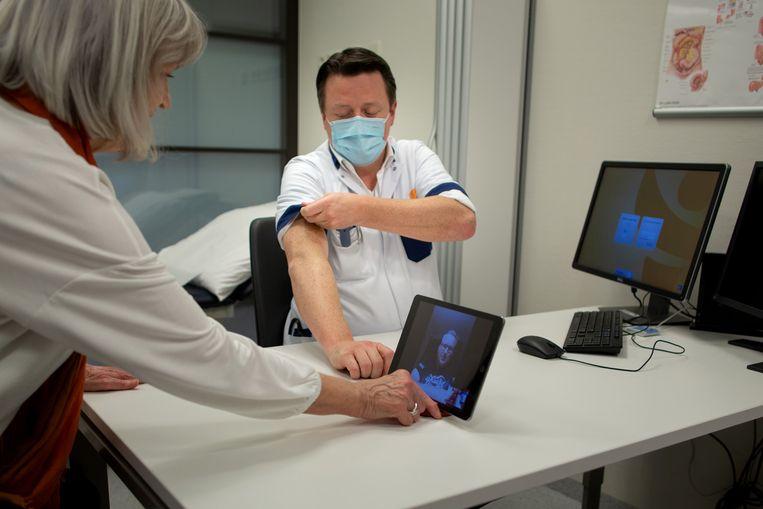 Bariatisch specialist Tim Verhagen en een patiënt via beeldbellen. Beeld Herman Engbers