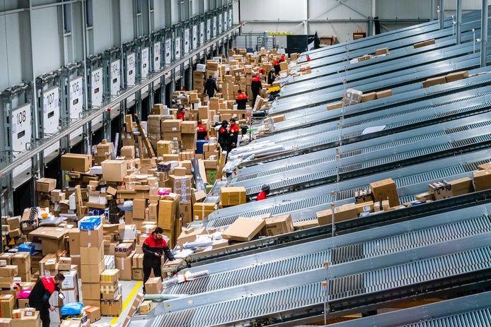 Medewerkers van een pakketdienst behandelen pakketjes in een pakkettensorteercentrum.
