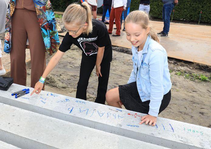 Maud Rammelaere (links) en Anna van de Ree van basisschool Op Dreef, schreven nog hun namen op de heipaal voor deze de grond in ging.
