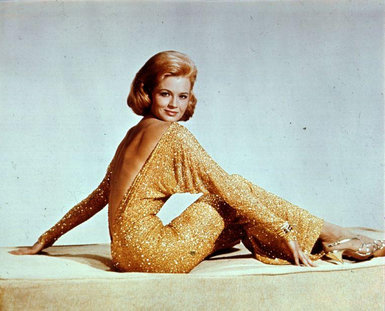 Actrice Angie Dickinson in goudkleurige avondjurk met open rug en vleermuismouwen. Beeld Getty