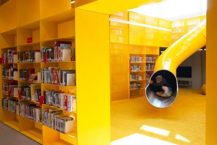 De grote gele glijbaan in de kinderafdeling van de bibliotheek is een hit.
