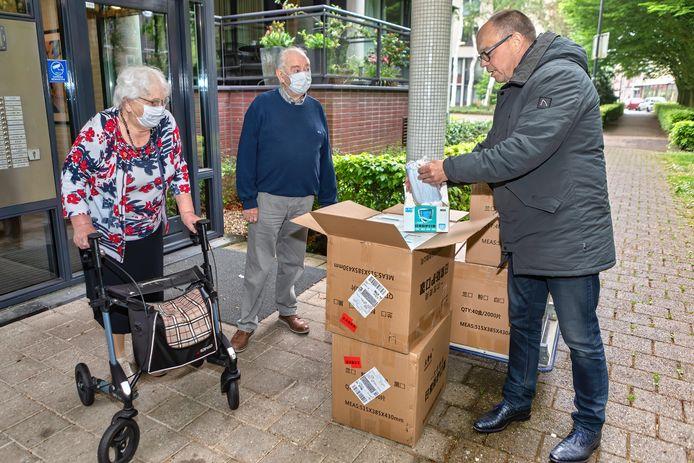 Wethouder Marcel Willemsen inspecteert onder toeziend oog van de ouders van Jan Peeters de mondkapjes die de oud--Oosterhouter aan zijn voormalige woonplaats schenkt.