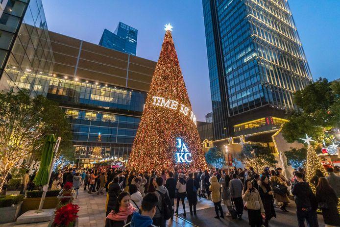 Chinezen rond een kerstboom in Shanghai. In een aantal Chinese steden is het vieren van Kerstmis verboden.