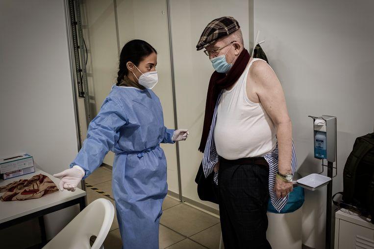 De 82-jarige Harald krijgt zijn covid-19-vaccinatie op de oude luchthaven Schönefeld. Beeld Daniel Rosenthal / de Volkskrant