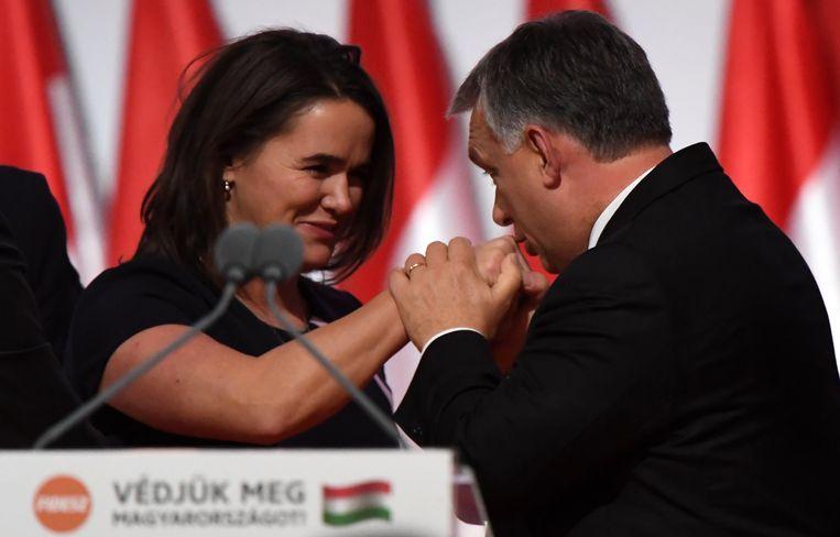Premier Viktor Orban kust de hand van zijn minister van Familiezaken Katalin Novak. Zij vraagt vrouwen te stoppen met het gedram dat ze evenveel moeten verdienen als mannen. Beeld AFP