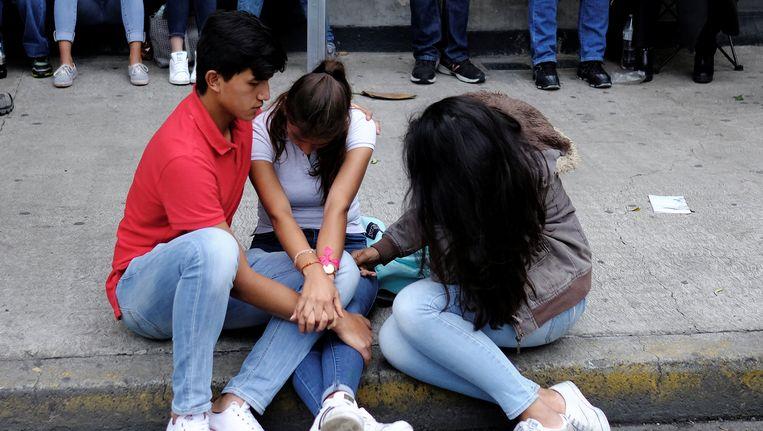 Familieleden rouwen bij een ingestort gebouw. Beeld reuters