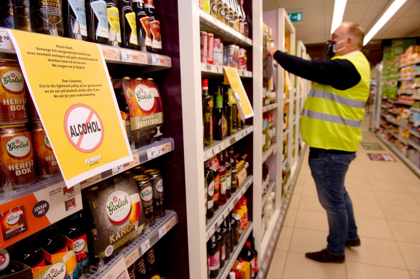 Een medewerker van de Jumbo zet de schappen af, omdat na 20 uur geen alcohol meer verkocht mag worden.