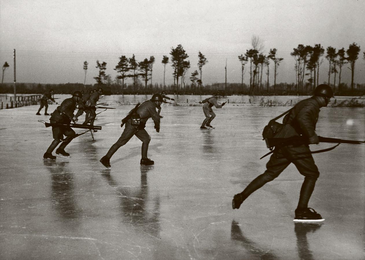 Schaatsende militairen bij Leusden op 11 januari 1940  Het land verdedigen op schaatsen: Nederlandse militairen op de schaats tijdens een oefening met wapens. In de omgeving van Leusden is het gebied geïnundeerd, waardoor ze zich gemakkelijk over het ijs konden verplaatsen.