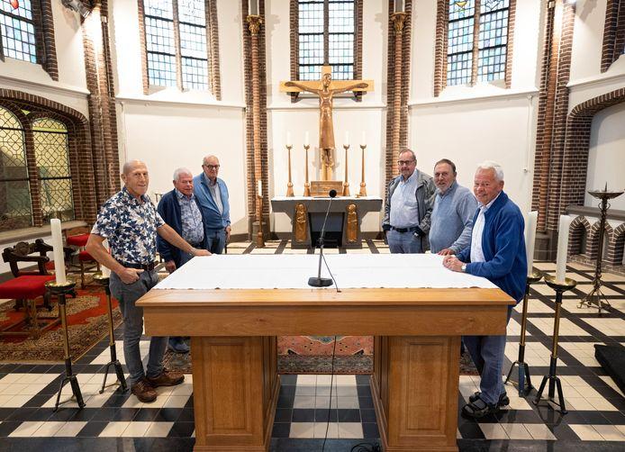 Enkele vrijwilligers die het nieuwe altaar gebouwd hebben, het oude altaar staat achterin het priesterkoor.