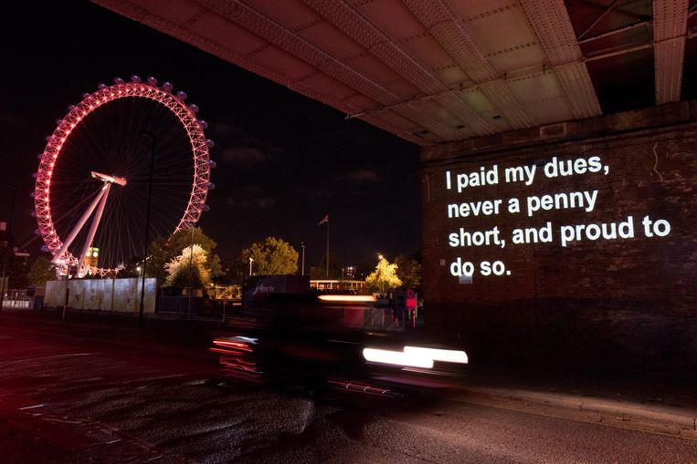 Tekst uit de film 'I, Daniel Blake' van Ken Loach, geprojecteerd op een muur in Londen. Beeld Getty Images