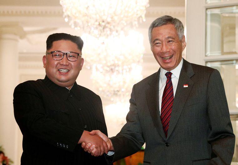 Kim Jong Un schudt zondag in Singapore de hand van minister-president  Lee Hsien Loong. Beeld REUTERS