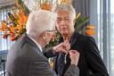 Derk Bolt krijgt een koninklijke onderscheiding opgespeld door zijn vader in aanwezigheid van burgemeester Femke Halsema.