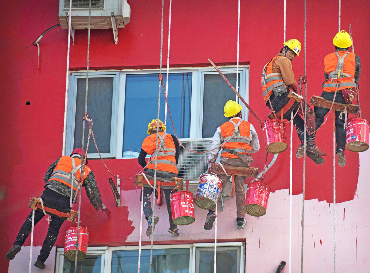 Chinese huisschilders in Beijing verven de buitenkant van een huis zonder  een steiger te gebruiken. Al hangend aan touwen lijkt het ook goed te gaan. Foto Fred Dufour