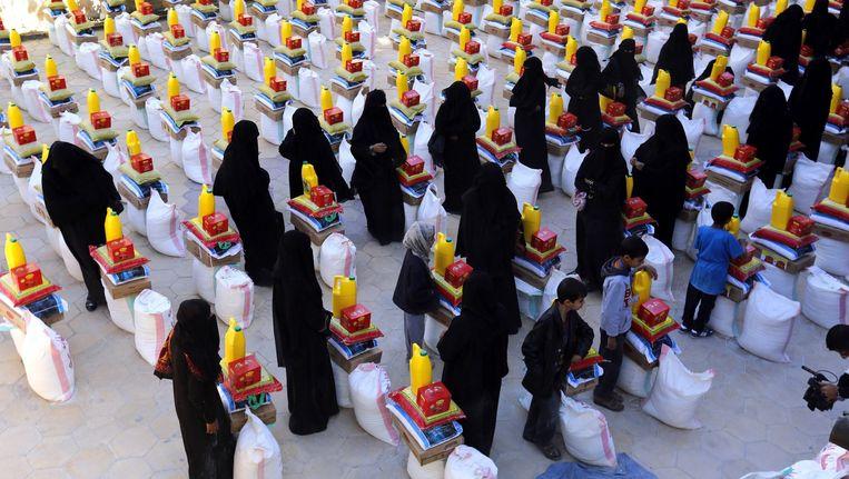 Gesluierde vrouwen staan naast hun voedselratsoen in de Jemenitische stad Sana'a. Beeld epa