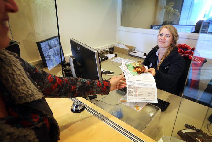 Archieffoto waarbij een medewerkster van de HAP Etten-Leur informatie-folders overhandigt aan een patiënt.