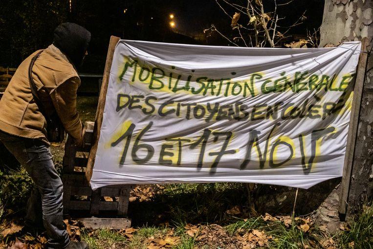 Vincent Coulon laat een grote banner zien bij zelfgebouwde hut zien bij de rotonde waar ze met een groep Gele Hesjes ieder weekend bijeenkomen Beeld Joris Van Gennip