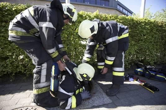Brandweermannen inspecteren de riolering.