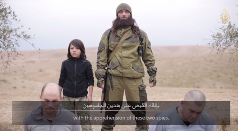 Still uit de IS-video waarin een jongen twee zogenaamde Russische spionnen doodschiet. Beeld Hayat Media