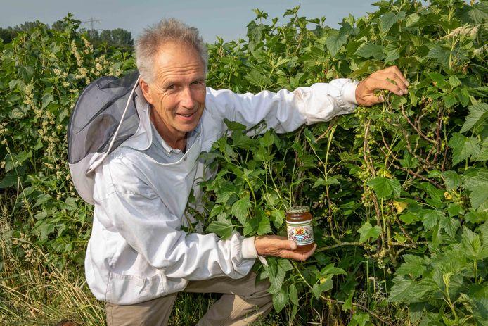 Imker Jan Koeman met honing van zwartebessenbloesem.