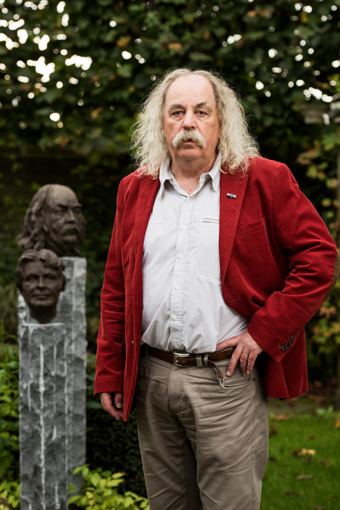 Paul Spapens in zijn tuin in Moergestel, naast een borstbeeld van hem en zijn vrouw Hennie.