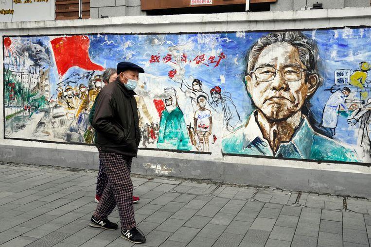 Op de muurschildering 'Herinneringen' staat de Chinese medisch expert Dr. Zhong Nanshan, die als eerste op staatstelevisie verklaarde dat het virus van mens op mens overdraagbaar is. Beeld AP