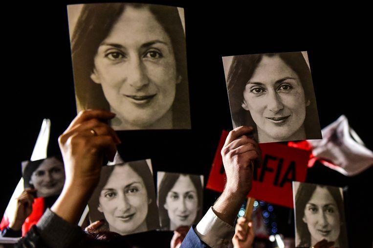 Bij een protest georganiseerd door Galizia's familie en burgerrechtenbewegingen op Malta deze week worden borden omhoog gehouden met 'Mafia Regering' erop. Beeld AFP