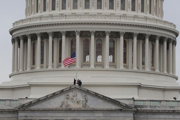 De Amerikaanse vlag op het Capitool hangt halfstok nadat een politieagent omkwam tijdens de bestorming van het Capitool afgelopen woensdag.  Beeld AFP