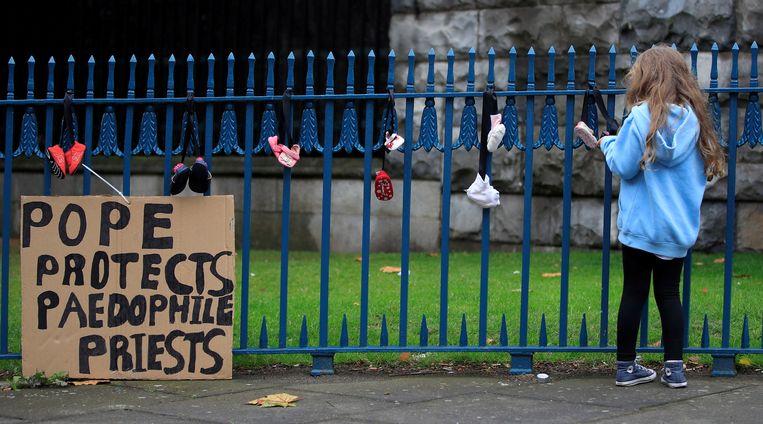 'De paus beschermt pedofiele priesters' staat te lezen op dit bord in Dublin. Er zijn als protest ook kinderschoentjes aan een hek vastgeknoopt. Beeld Reuters
