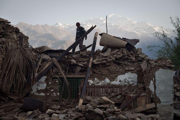Een inwoner van het dorp Barpak loopt over de restanten van zijn huis. Beeld AFP