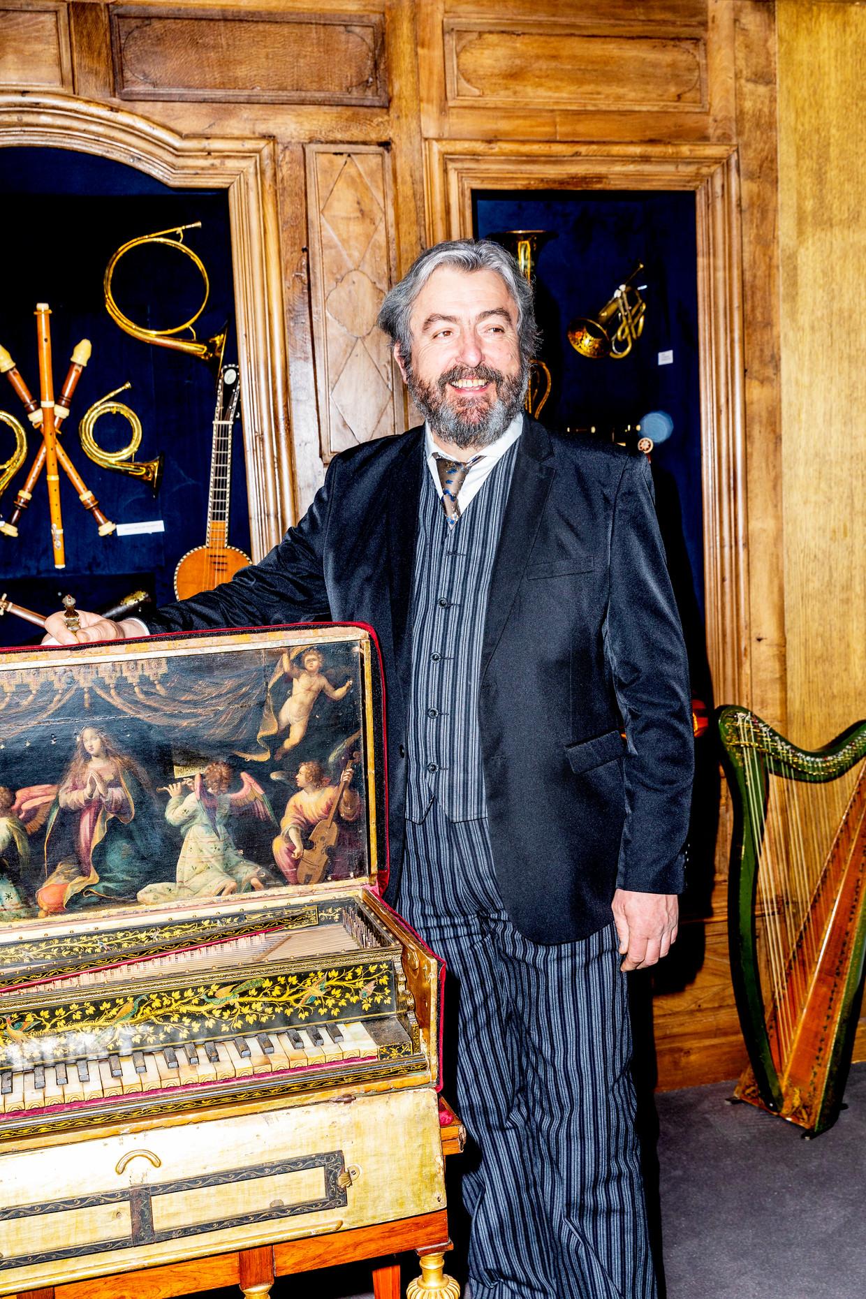 Jean Michel Renard, handelaar in antieke muziekinstrumenten uit Bellenaves, naast een 16de-eeuws Italiaans spinet van cypressen- en vurenhout. Beeld Marie Wanders