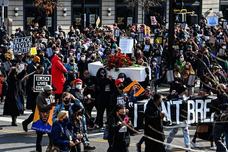 Demonstranten verzamelden zich zondag in Minneapolis, de dag voordat het proces begint tegen Derek Chauvin, de agent die ruim acht minuten zijn knie in de nek van George Floyd drukte. Beeld CHANDAN KHANNA /AFP