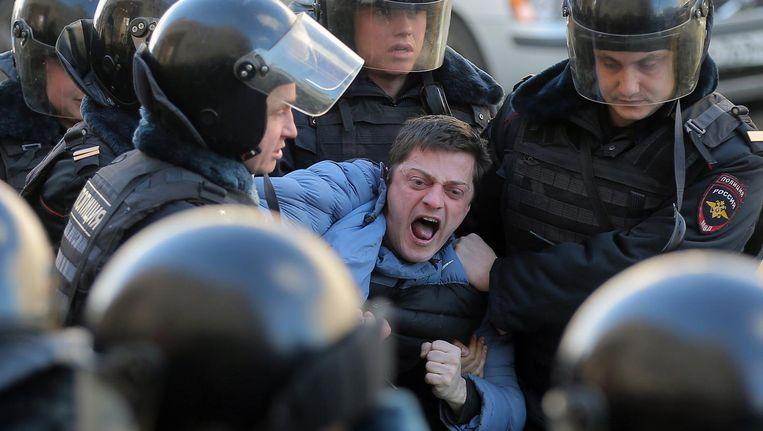 De politie arresteert een demonstrant tijdens het protest afgelopen zondag in Moskou. Beeld epa
