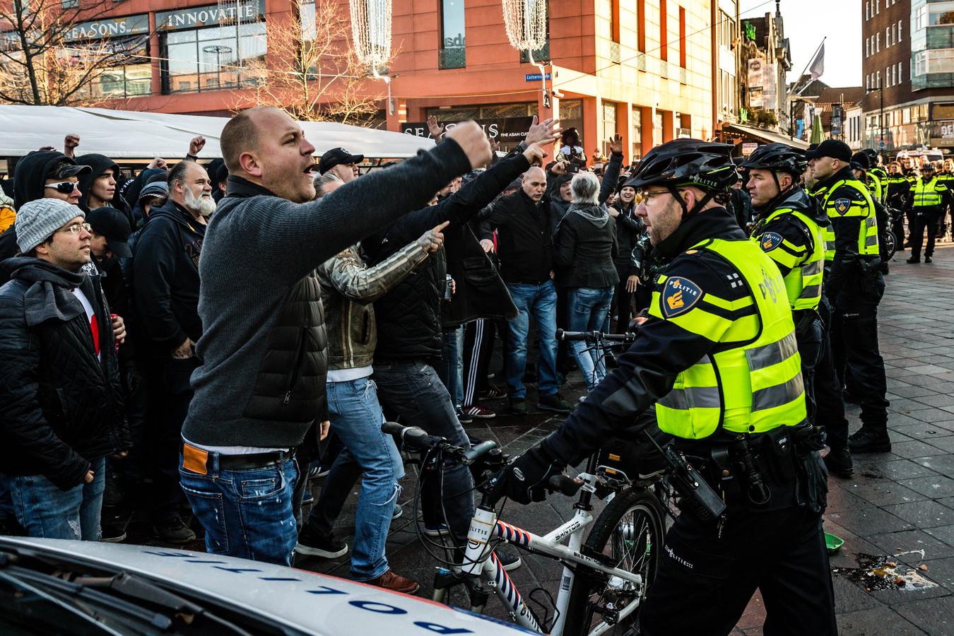 Hooligans (links) proberen bij de KOPZ-demonstratie op het Catharinaplein te komen maar worden tegengehouden door agenten. (archieffoto).